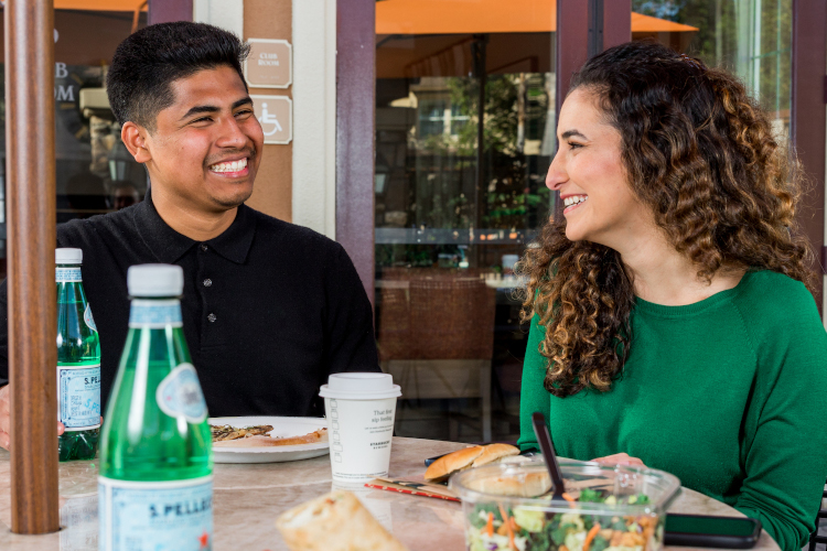 Two people smiling and eating at a table