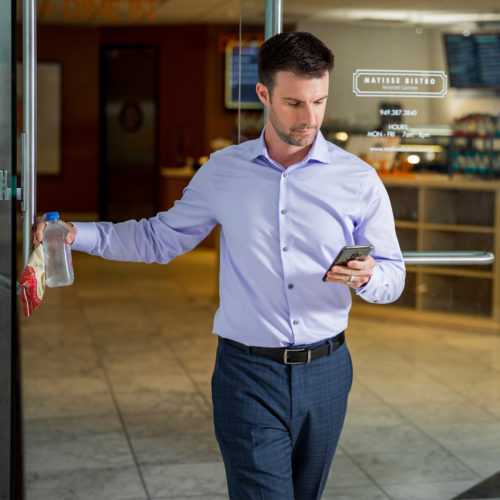 Man walking out of store looking at phone