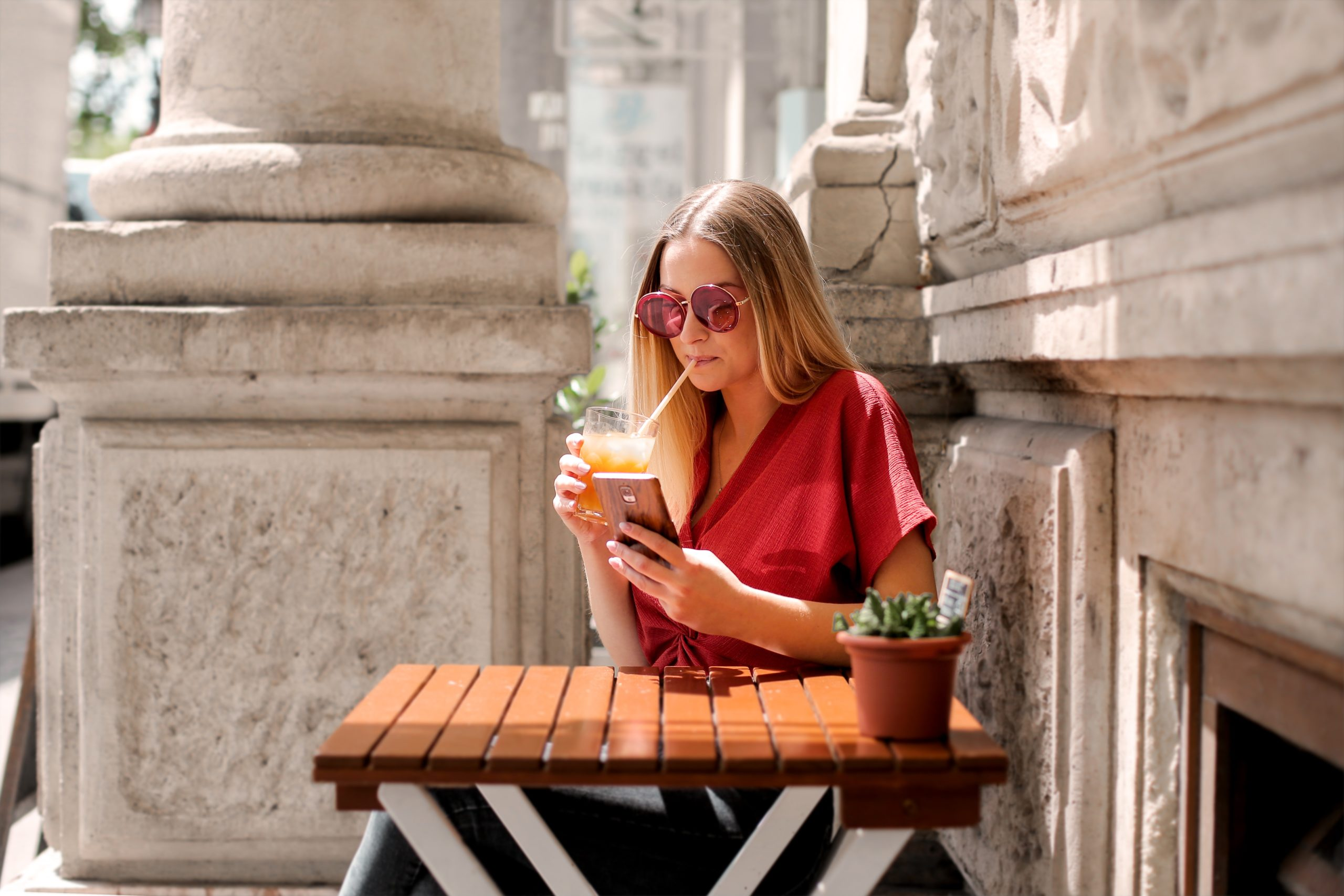 woman-drinking-while-holding-smartphone-3768115