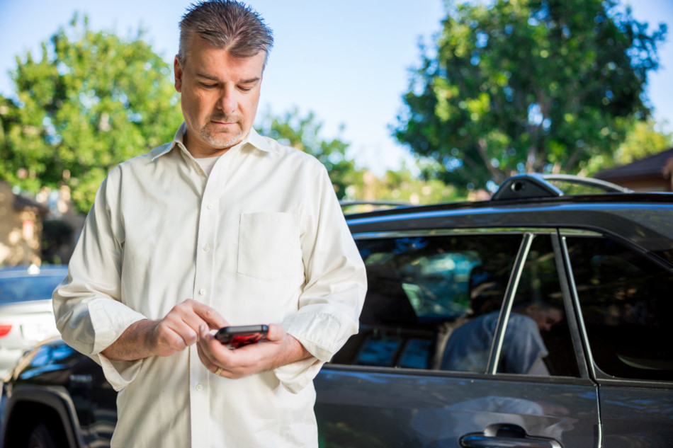 Man touching phone screen in front of car