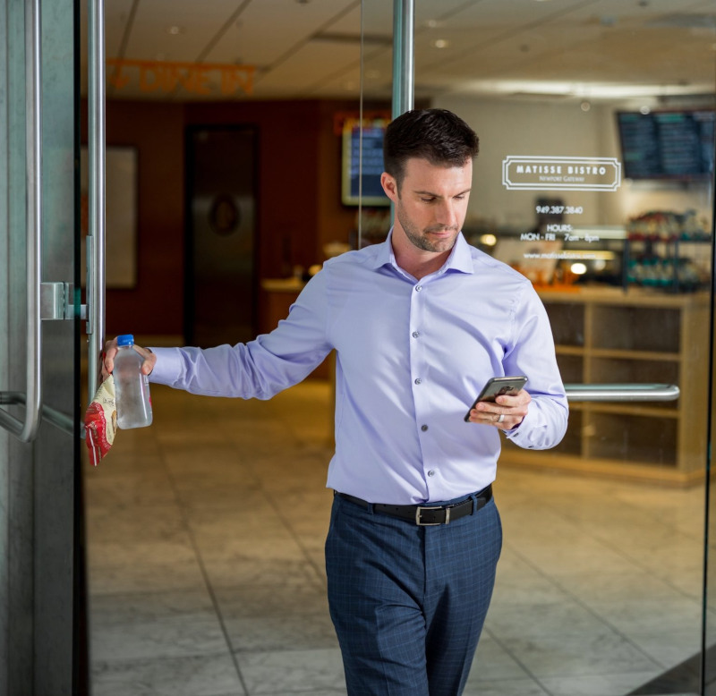 Man leaving store with chips and looking at phone